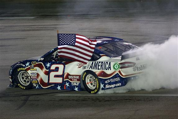 Photo Courtesy of: 299489Todd Warshaw/Getty Images. Brad Keselowski, driver of the #2 Miller Lite Ford, celebrates with a burnout after winning the NASCAR Sprint Cup Series Quaker State 400 presented by Advance Auto Parts at Kentucky Speedway on June 28, 2014 in Sparta, Kentucky.
